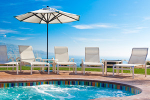 Jacuzzi pool, lounge chairs and umbrella with view of Pacific ocean