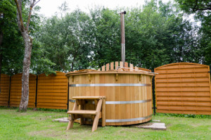 rustic wooden water spa hot tub with stairs in garden yard