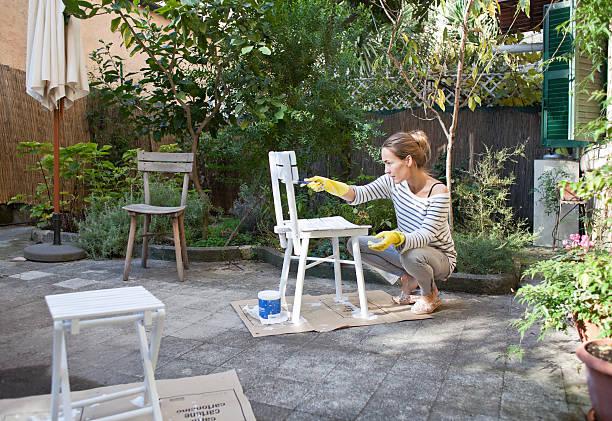 Jeune femme qui repeint son mobilier de jardin en bois